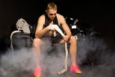 Boxer bandaging his hands in a smoky room — Stock Photo