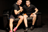 Twee gelukkige passen jonge mannen die een arm worstelen — Stockfoto