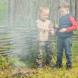 Two young boys play alongside a smoking fire — Stock Photo #45196463