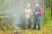 Two young boys play alongside a smoking fire — Stock Photo