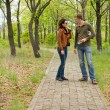 Young couple standing talking in a park — Stock Photo