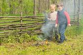 Proud little boys standing watching a burning fire — Stock Photo