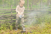 Little boy trying to extinguish a fire — Stock Photo