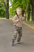 Determined macho little boy stick fighting — Stock Photo