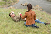 Romantic young couple relaxing near a river — Stock Photo