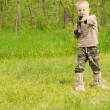 Постер, плакат: Little boy pointing an automatic weapon