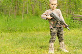Small boy playing with a gun — Stock Photo