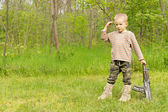 Little boy playing at soldiers standing saluting — Stock Photo