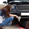 Woman helping a mechanic fix her car — Stock Photo