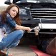 Attractive trendy young woman fixing her car — Stock Photo
