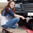 Woman kneeling in front of her broken down car — Stock Photo