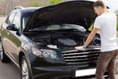 Male driver checking his car engine — Stock Photo