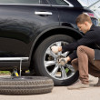 Young man changing the punctured tyre on his car — Stock Photo #46244047