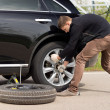 Young man struggling to change his car tyre — Stock Photo #46244049