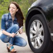 Smiling young woman getting ready to change a tyre — Stock Photo