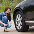 Young woman checking out a flat tyre on her car — Stock Photo