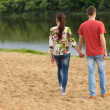 Young couple walking towards the edge of the lake — Stock Photo #46244401