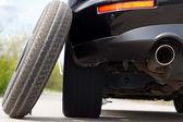 Spare tyre balanced against a car — Stock Photo