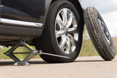 Jacking up a car to change a tyre — Stock Photo