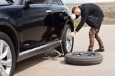 Male driver struggling to change his car tyre — Stock Photo