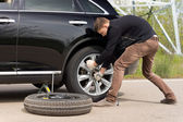 Young man struggling to change his car tyre — Stock Photo