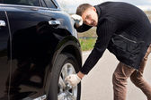 Young man battling to change the tyre on his car — Stock Photo