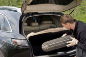 Man removing his spare tyre from the boot — Stock Photo