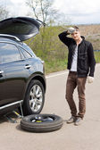 Man with a puncture changing a tyre — Stock Photo