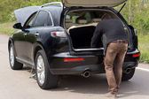 Homem à procura de ferramentas no porta-malas de seu carro — Foto Stock