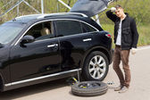 Male driver changing his car tyre after a puncture — Stock Photo