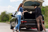 Young couple getting ready to change a tyre — Stock Photo