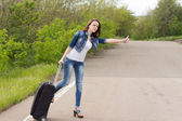 Woman with a suitcase thumbing a lift — Stock Photo