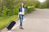 Young woman holding a trolley while hitchhiking — Stock Photo