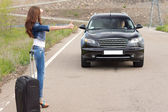Woman hitchhiking after a breakdown with her car — Stock Photo