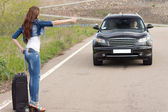 Trendy woman hitchhiking on a country road — Stock Photo