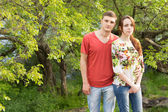 Loving young couple in lush woodland — Stock Photo