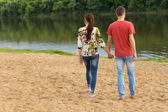 Young couple walking towards the edge of the lake — Stock Photo