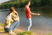 Young man skimming stones across water — Stock Photo