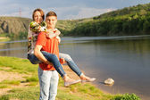 Young man giving his girlfriend a piggy back — Stock Photo
