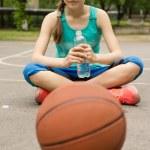 Athletic teenage girl drinking bottled water — Stock Photo