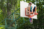 Agile ragazza giovane di fissaggio di una rete su un obiettivo di basket — Foto Stock