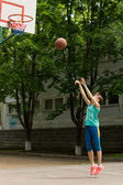 Teenage girl playing basketball — Stock Photo