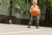 Determined young boy playing basketball — Stock Photo