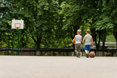 Two young boys walking off a basketball court — Stock Photo
