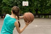 Young slender teenage girl playing basketball — Zdjęcie stockowe