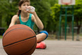 Young basketball player drinking water — Stock Photo