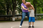 Mother teaching her son to play basketball — Стоковое фото
