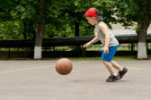 Small boy bouncing a basketball on a court — Stock Photo