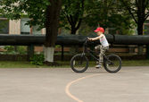 Young boy riding his bike on a basketball court — Stock Photo