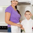 Smiling mother and son in chefs outfits — Stock Photo #47724971